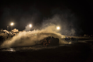 Water protectors ignite fires for warmth for hypothermic victims of water cannons and as a symbol of sacred fire and tradition. They use blue tarps to protect the fires from the law enforcement water hoses.
